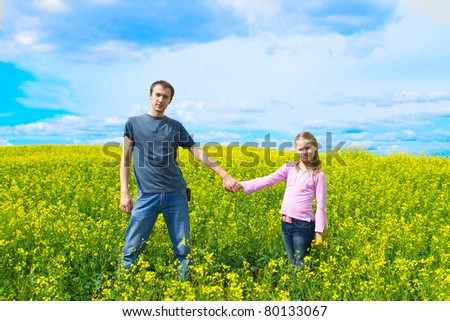 The father with a daughter on a meadow - stock photo