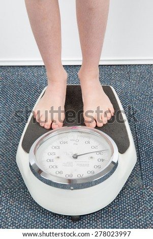 The feet of a girl standing on a bathroom scale - stock photo