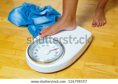 the feet of a woman standing on a bathroom scale - stock photo