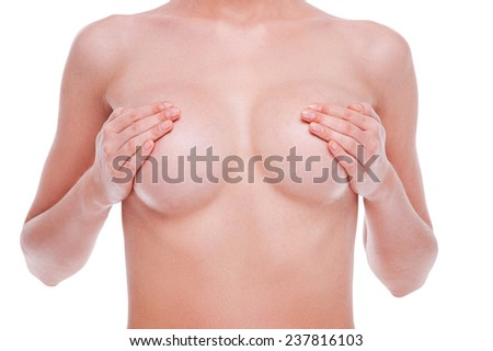 The female form is beautiful. Close-up of young naked woman covering her breast while standing against white background  - stock photo