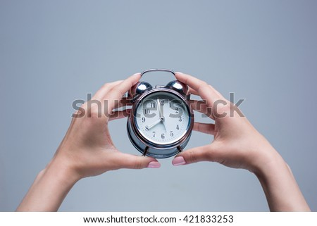 The female hands and old style alarm clock on gray background - stock photo