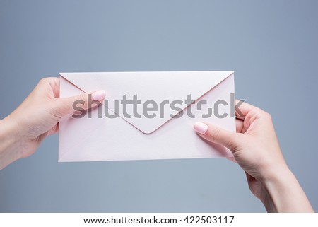 The female hands with envelope against the gray background - stock photo