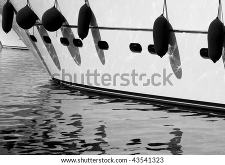 The fenders on a yacht in St Tropez reflect in the water of the harbor - stock photo