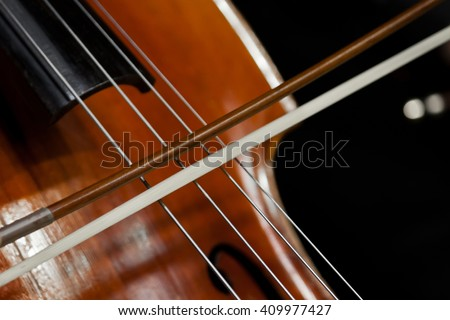 The fiddlestick on the strings of the cello closeup - stock photo