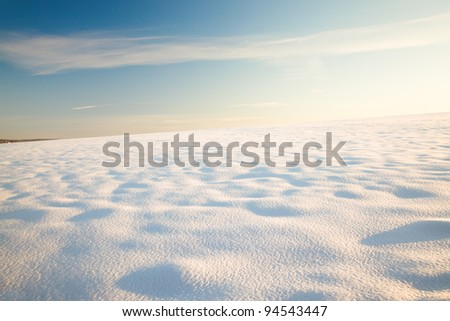 The field covered with snow in a winter season. A sunny day. The field all is covered by high snowdrifts - stock photo
