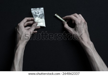 The fight against drugs and drug addiction topic: addict hand holding package of cocaine and wrapped dollar to sniff on a dark background in the studio - stock photo