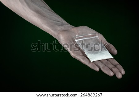 The fight against drugs and drug addiction topic: dirty hand holding a bag addict cocaine on a dark green background in the studio - stock photo