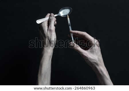 The fight against drugs and drug addiction topic: hand holding a syringe and a drug addict gains from a spoon liquid drug on a dark background - stock photo