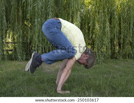 the figure of a young man on a background of green trees - stock photo