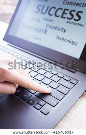 The Finger pressed the Enter button on laptop to success the business concept - stock photo