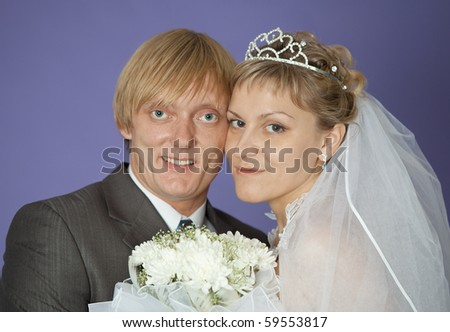 The first family portrait of the groom and the bride on violet background - stock photo