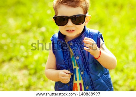 The first investment concept. Portrait of a stylish happy baby boy with ginger (red) hair holding coins in the park. Hipster style. Sunny weather. Copy-space. Outdoor shot - stock photo