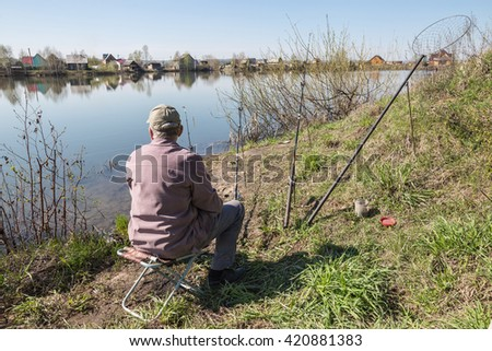 The fisherman catches a fish in the river in the spring - stock photo