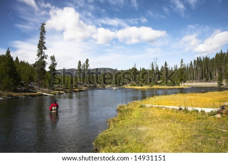 The fisherman in a red diving suit with auto heating in the cold autumn river - stock photo