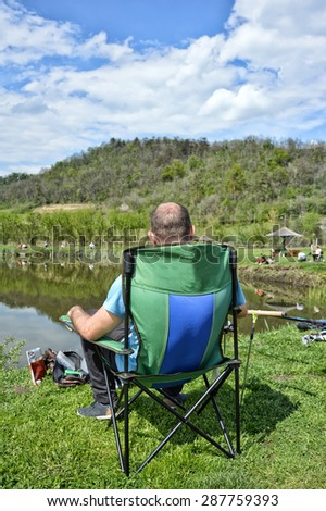 The fisherman sits on a stool a back on the lake - stock photo