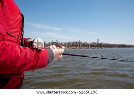 The fisherman with a bait casting reel - stock photo