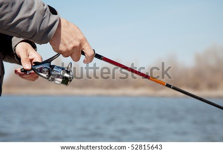The fisherman with a fishing reel - stock photo