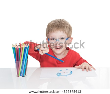 The five-year-old boy in blue points sits at a white table and and draws pencils,  isolated on a white background - stock photo