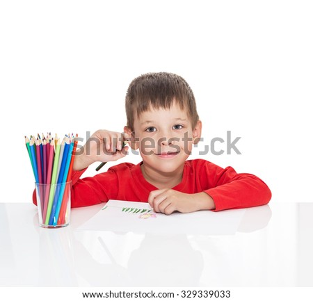 The five-year-old boy sits at a white table and draws pencils, isolated on a white background - stock photo