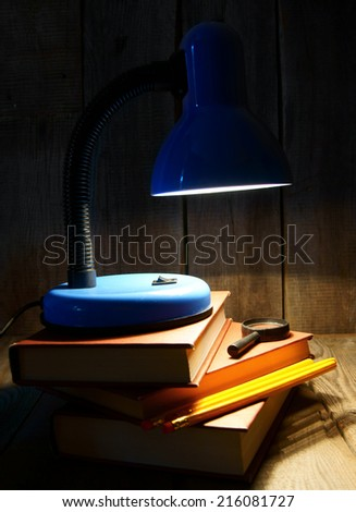 The fixture, books and a magnifier. On a wooden background. - stock photo