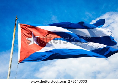 The flag of Cuba waving in the wind against a blue sky. - stock photo