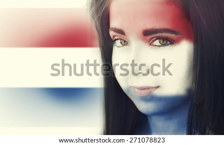 The flag of Netherlands on the face of a smiling woman. / Color effects and custom white balance is added to this photo. - stock photo