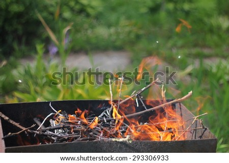 the flames of the open fire grill outdoors  - stock photo