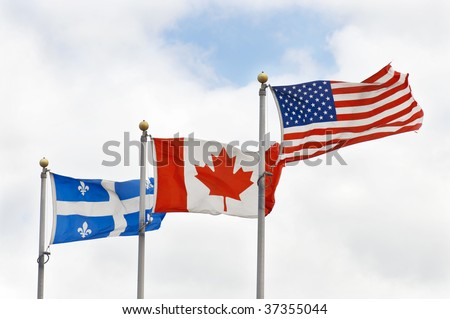 The fluttering in the wind, the flags of USA, Canada and Quebec on the background of the cloudy sky. - stock photo