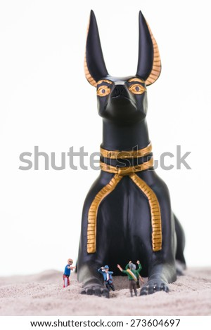 The focus is on the miniature tourists with the Egyptian God Anubis statue as background  - stock photo