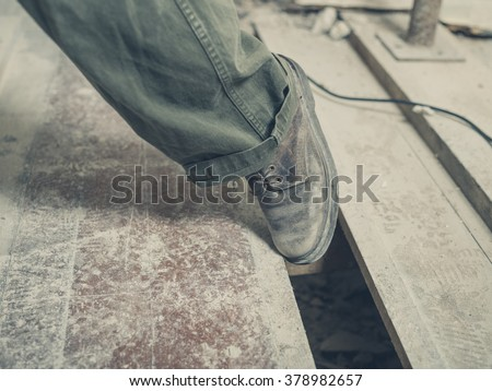 The foot of a person tripping on a gap between the floor boards in a room undergoing renovations - stock photo
