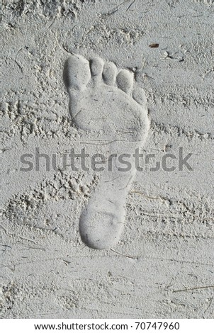 The footprint is in the sand that is on the beach - stock photo
