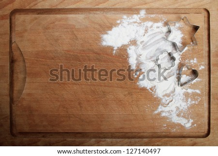 The form for cookies on the wooden board poured by a flour - stock photo