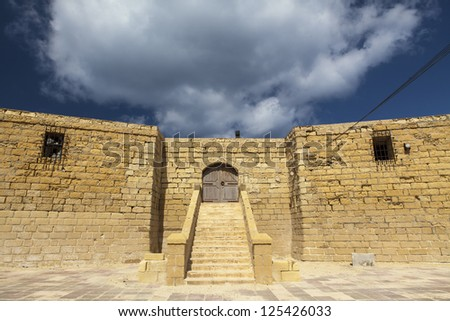The fortified tower in Qbajjar, Gozo. Built in 1716 by engineers Jacques de Camus D�¢??Arginy and Bernard de Fontet, it now lays in a state of abandon after being used as a bar, restaurant and disco. - stock photo