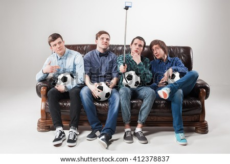 The four guys with balls on gray background - stock photo