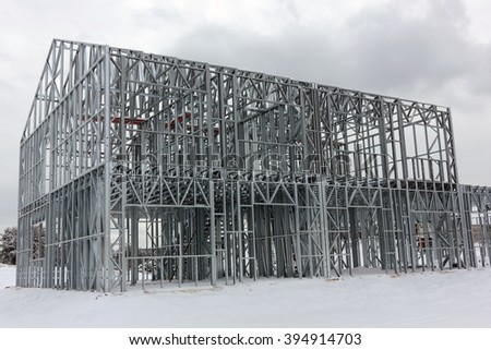 The framework of the modern rural house is made of galvanized metal beams and profiles. Winter day landscape - stock photo