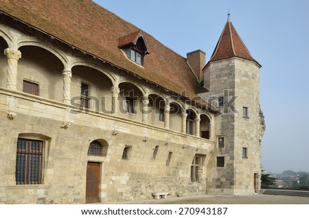 The French ancient castle of the Renaissance style is located in the town Nerac. This is a wing of the original fortress with a round tower and an arcaded balcony with decorative columns. - stock photo