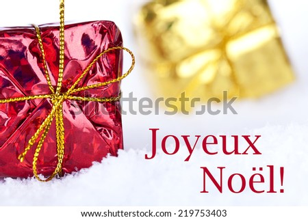 The French Christmas Greetings Joyeux Noel which means Merry Christmas in the Snow with Christmas Gifts - stock photo