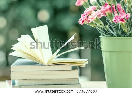 the fresh pink carnation flower with books - stock photo