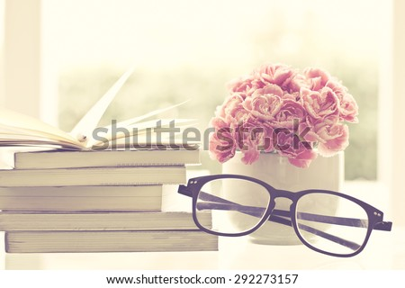 the fresh pink carnation flower with books and old glasses background - stock photo
