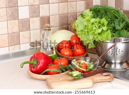 The fresh washed-up vegetables in a colander and the cut vegetables on a chopping board against modern kitchen. - stock photo