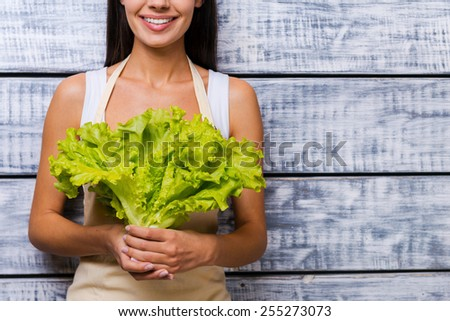 The freshest lettuce for you. Cropped image of beautiful young woman in apron holding fresh lettuce and smiling while standing in front of wooden background - stock photo
