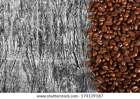 the fried beans of coffee on a wood background - stock photo
