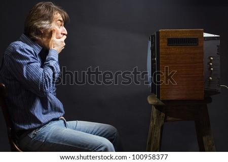 The frightened man watching TV. - stock photo