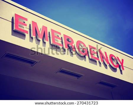 the front entrance sign to an emergency room department in a city hospital toned with a retro vintage instagram filter effect app or action  - stock photo