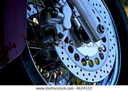 The front wheel of a motorcycle with lots of chrome. - stock photo