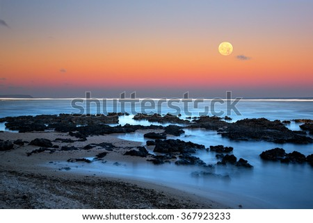 The full moon rising over the ocean as the sun sets and the sky turns pink and yellow on a cloudless evening over the island of Guam - stock photo