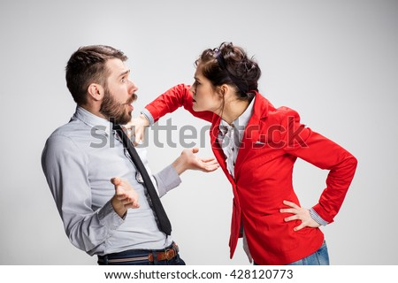 The funny angry business man and woman conflicting on a gray background. Business concept of relationship of colleagues - stock photo