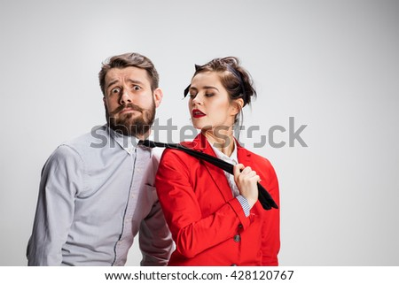 The funny business man and woman cooperating on a gray background. Business concept of leadership of colleagues - stock photo