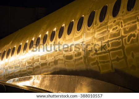 The fuselage of a modern passenger plane.  Aircraft painting in the gold colors of night Airport lightening. - stock photo