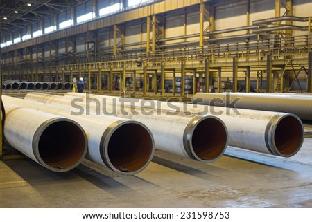 The gas supply pipes of large diameter are stacked in workshop - stock photo